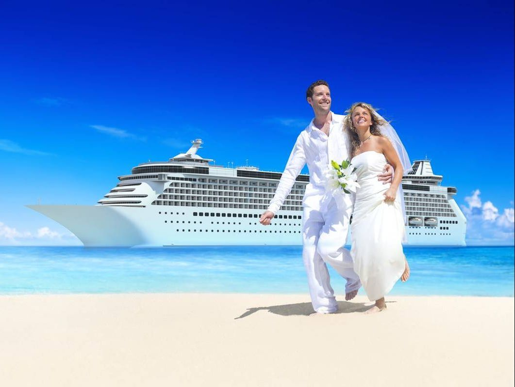 Newlyweds in front of cruise ship a beach shore
